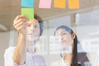 Businessman and businesswoman sticking adhesive notes on glass wall in office.jpeg