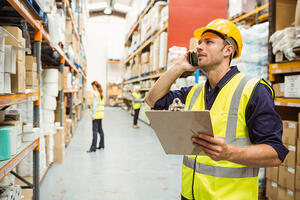 Warehouse worker talking on the phone holding clipboard in a large warehouse-2
