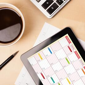 Workplace with tablet pc showing calendar and a cup of coffee on a wooden work table close-up-291558-edited.jpeg